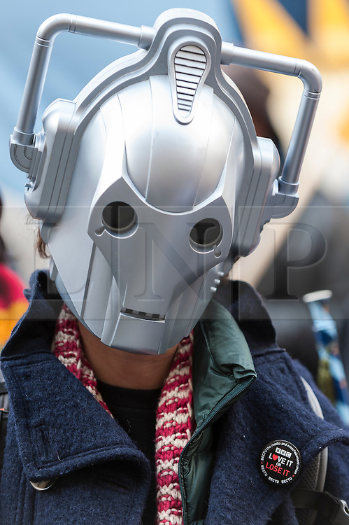 """© Licensed to London News Pictures. 23/11/2015. LONDON, UK. A person wears a Cyber Man mask as fans of Doctor Who known as """"Whovians"""" and other supporters of the BBC gather outside Broadcasting House in central London to oppose the threat of 20% government cuts to the Corporation. Photo credit : Stephen Chung/LNP"""