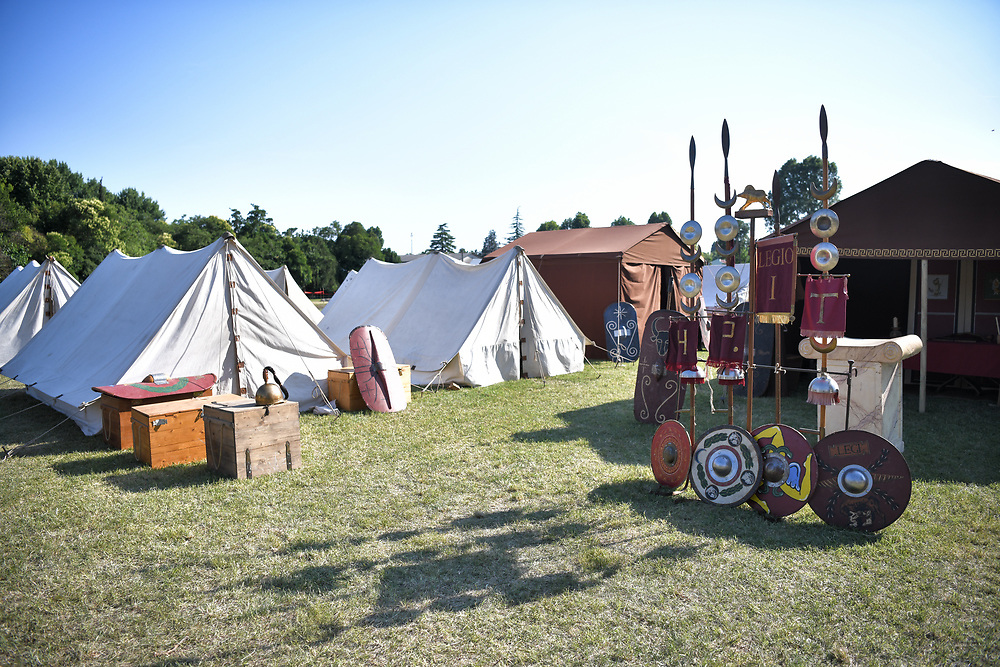 Aquileia, Italy - 17 June 2018: Roman legionary camp with tent, shields, helmets and army insignia during the Tempora in Aquileia, ancient Roman historical re-enactment