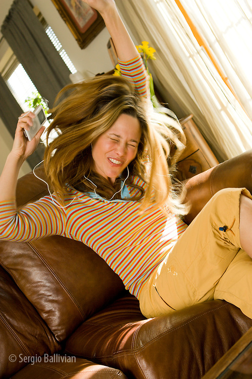 A young woman listens to an iPod in her home and dances and entertains herself.