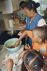 Parents and two children cooking together in kitchen,