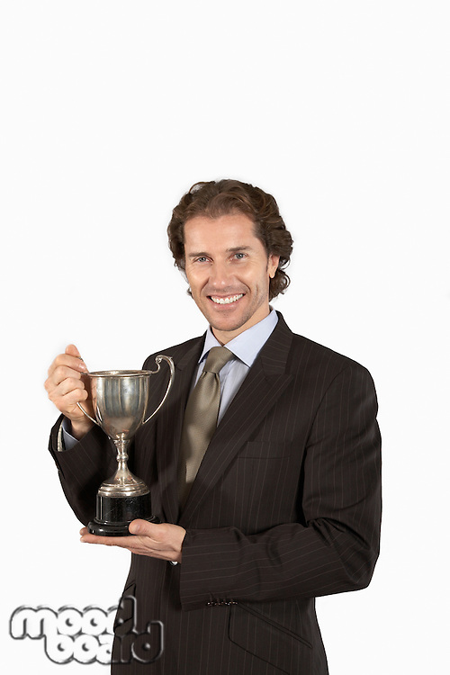 Businessman holding trophy smiling on white background portrait