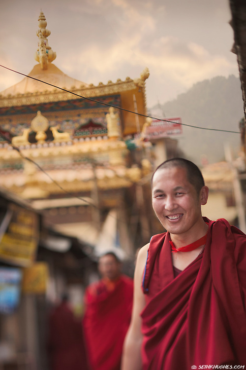 A Tibetan monk stands under an eave on the streets of McLeodGanj, Dharamsala, India.