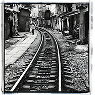View of the railway of Hanoi. In this place buildings and houses are constructed along the railway. Houses are quite precarious. A kid walking greets the photographer.
