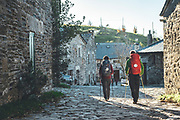 Backpackers couple walking a stage in Camino de Santiago, Galicia, Spain