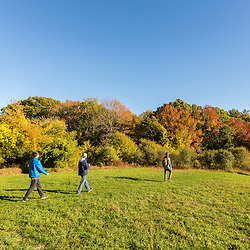 Three young men walk on a hilltop field in Amesbury, Massachusetts.