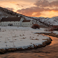 Winter sunset along a stream running through Park City, Utah next to the famous Park City barn set against the Eastern back of the Wasatch Mountains.