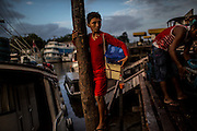 Antonio, 12 balances on the wood pillars of an informal dock as he tries to sell staples in Santana village, near Macapa, Brazil, Tuesday, Oct. 25, 2016.  Bathed by the Amazon river mouth  this northernmost capital of 400.000 residents is as filled with canals, informal docks and unregistered boats as it lacks infrastructure and control means for fighting the rising river piracy plaguing passengers and transportation companies. (Dado Galdieri for The New York Times)
