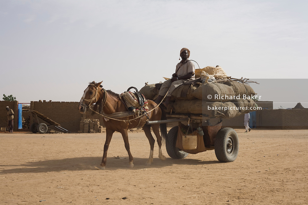 Horse and trailer makes its way across barren earth in the 4 sq km Abu Shouk refugee camp which is (disputedly) home to 38,000 displaced persons and families on the outskirts of the front-line town of Al Fasher (also spelled, Al-Fashir) in north Darfur. .