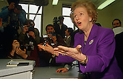 Margaret Thatcher plays up to the media at a North London school in her own constituency of Finchley during the 1992 general election. Although Thatcher had already resigned as Prime Minister in November 1990, John Major won the ensuing leadership election later that year. Photographers and cameramen surround the former-Prime Minister who is wearing a purple suit and matching broach. She is mid-sentence and has found something amusing to respond to the chants of the media. We see cameras, sound booms and flashes all prepared to photograph this famous statesman including Tom Stoddart who is making eye-contact with the viewer.