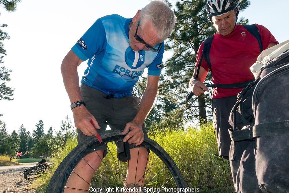 BC00633-00...BRITISH COLUMBIA - David Grim and Greg Scallon fixing a flat at the campsite in Kikomun Provincal Park.