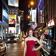 Bat Mitzvah girl stands in Times Square,NYC  street at night