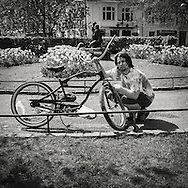 Young man washing his bike in the garden in front of Bergen theater on a sunny day