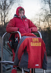 © Licensed to London News Pictures. 29/11/2016. London, UK. A lifeguard is wrapped up against the cold as he watches over swimmers at the outdoor heated Hampton Pool. Sub zero temperatures are due to spread to the south east this week as winter starts to set in. Photo credit: Peter Macdiarmid/LNP