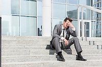 Full length of depressed businessman sitting on steps outside office