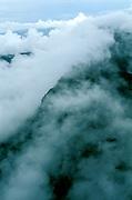 Aerial of low mountain emerging among clouds in Guyana Highlands, Venezuela.