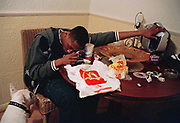 G.B. ENGLAND. London. Isle of Dogs. An MC listens to music after his McDonalds dinner, east London. 2005.
