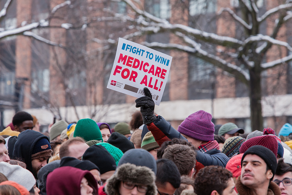 """Brooklyn, NY - 2 March 2019. A man holds high a sign that reads """"Fight to win medicare for all!"""" at Bernie Sanders' first rally for the 2020 presidential primary at Brooklyn College."""