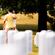 "Dana Kelly hugs her husband Colin Kelly, (both of Austin, TX) while visiting Arlington National Cemetery in Arlington, VA on Saturday, July 25, 2009.  Mr. Kelly served as an Infantry officer in the 1st Battalion, 506th Regiment, ""B"" Company in Iraq in 2004 and 2005 and visits a fallen comrade once a year."