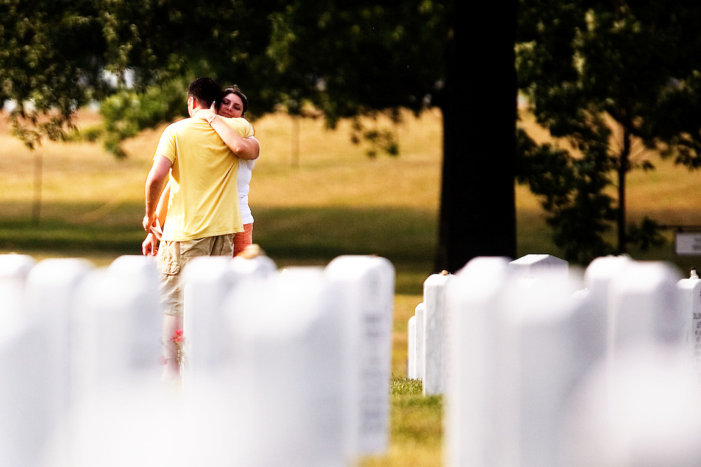 """Dana Kelly hugs her husband Colin Kelly, (both of Austin, TX) while visiting Arlington National Cemetery in Arlington, VA on Saturday, July 25, 2009.  Mr. Kelly served as an Infantry officer in the 1st Battalion, 506th Regiment, """"B"""" Company in Iraq in 2004 and 2005 and visits a fallen comrade once a year."""