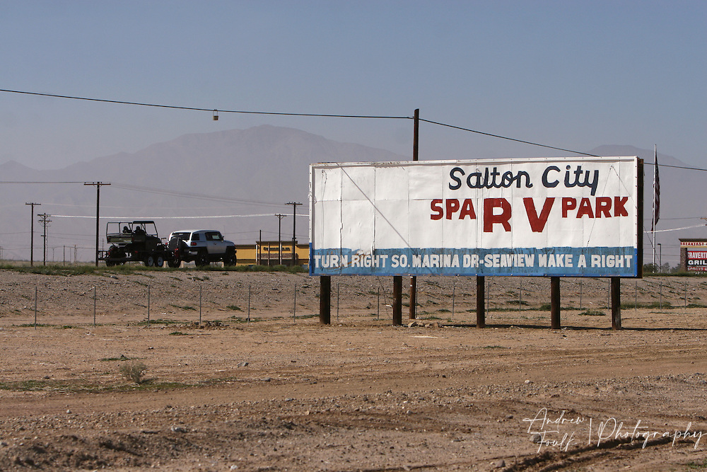 An SUV heads north on highway 86S passing a sign that used to bring tourist in to Salton City during the good old days.