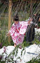 © Licensed to London News Pictures. 08/07/2013. London, UK. A Japanese girl plays on rocks in a garden entitled 'Spirits of the Land' by Mariko Naka the press view for the Royal Horticultural Society's Hampton Court Palace Flower Show today (08/07/2013). Photo credit: Matt Cetti-Roberts/LNP