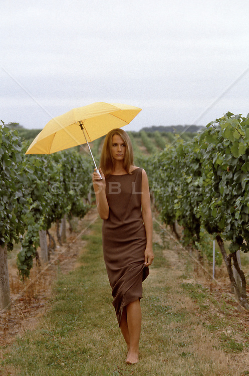 woman walking through a vineyard with an umbrella
