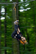 Town of Wallkill, New York - Jaida Macaluso flies upside down on  a zip line while during a Ninja Warrior Day Camp trip to Ring Homestead Camp on July 8, 2014.