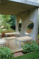 Covered concrete seating area with decking floor and oval 'windows'