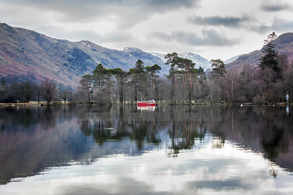 © Licensed to London News Pictures. 13/03/2018. Glenridding UK. A moored boat sits in the still water of Ullswater lake in Glenridding this morning on a mostly over cast day in Cumbria as the UK prepares for more freezing temperatures in the coming days. Photo credit: Andrew McCaren/LNP