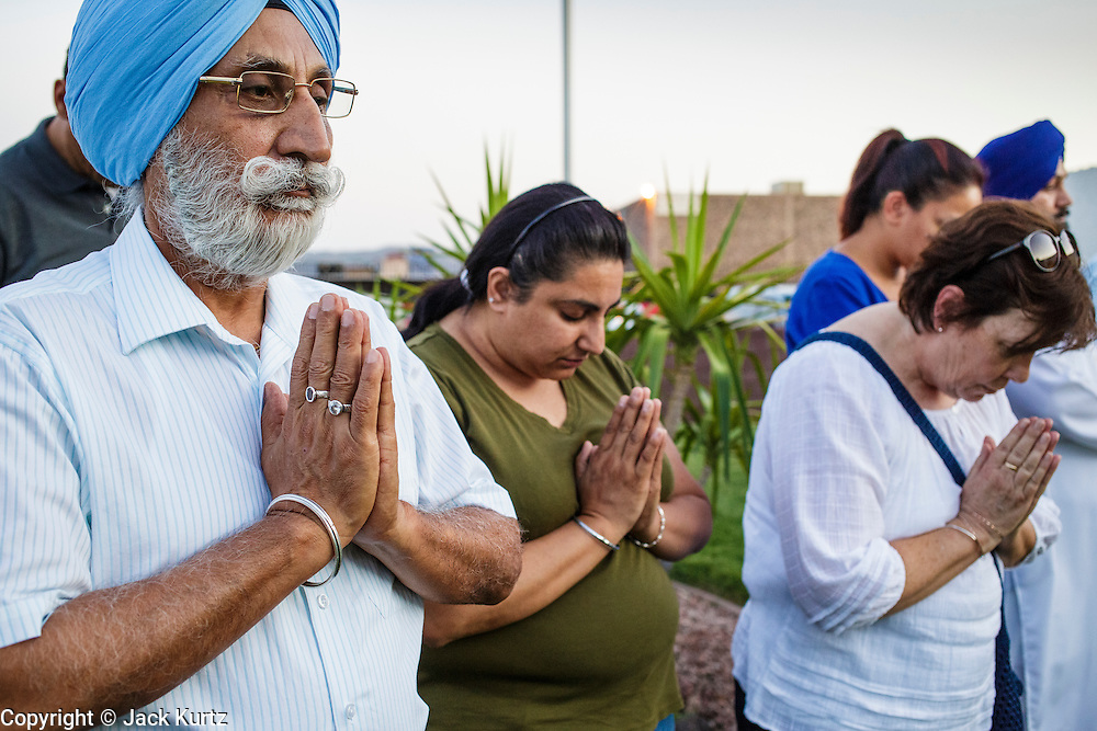 07 AUGUST 2012 - PHOENIX, AZ:    Members of the Sikh community in Phoenix pray during service at the Arizona Interfaith Movement offices in Phoenix Tuesday. Arizona Interfaith Movement consists of 25 different faith traditions. They hosted an interfaith Prayer Circle Tuesday night where attendees offered moments of prayer in their own faith tradition for the victims of the massacre at the Sikh temple in Wisconsin last Sunday. About 60 people attended the service.   PHOTO BY JACK KURTZ