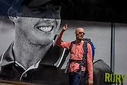 Man passes a Nike retail poster of Northern Irish golfer Rory McIlroy, in central London.