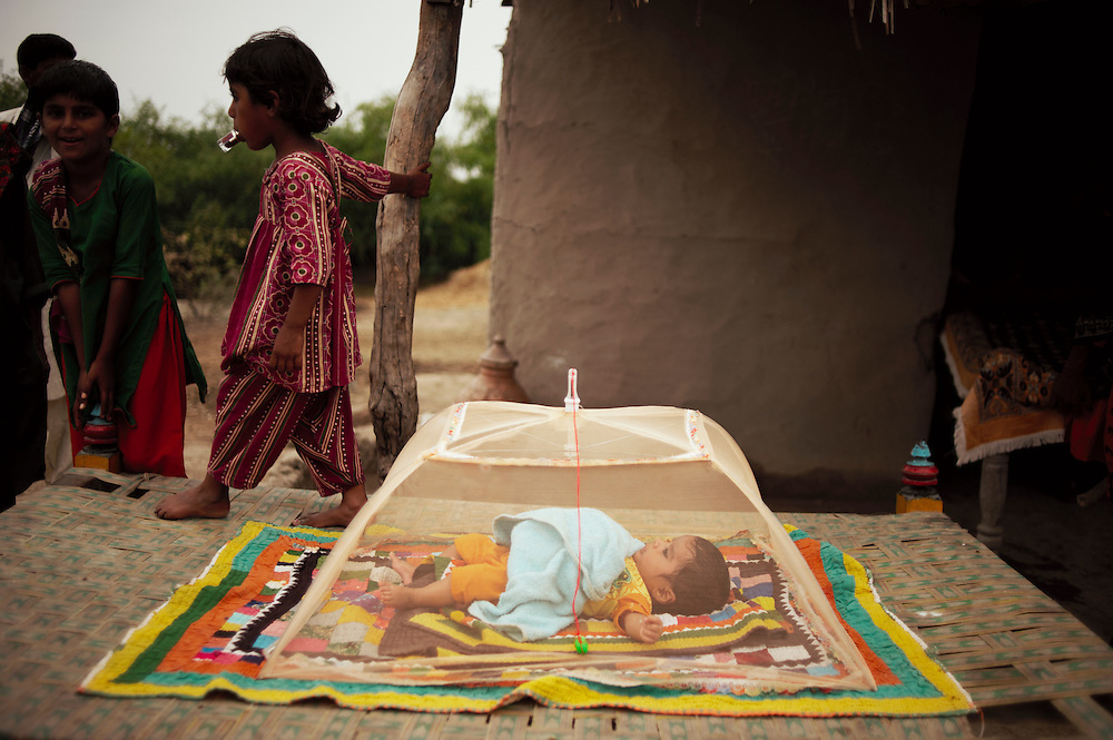Shamin 23 adjusts a mosquito net over her baby Namatullah, 2 months old in the village of Juman Namllah, A displaced flood communitY in Badin District, Sindh, Pakistan on November 2,  2011. Her family's home was submerged during recent floods. Health kits and education in hygiene have been conducted by Oxfam in the village. In August 2011, Heavy monsoon rains triggered flooding in lower parts of Sindh and northern parts of Punjab.