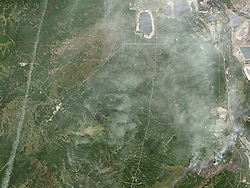 A destructive wildfire burned through Canada's Northern Alberta region, razing neighborhoods in Fort McMurray and displacing tens of thousands of residents.<br /> At 12:34 p.m. local time on May 3, 2016, the Operational Land Imager (OLI) on the Landsat 8 satellite acquired this false-color image of the fire. The image combines shortwave infrared, near infrared, and green light (OLI bands 7-5-3). Near- and short-wave infrared help penetrate clouds and smoke to reveal the hot spots associated with active fires, which appear red. Smoke appears white and burned areas appear brown.<br /> When this image was acquired, the fire was burning southwest of downtown Fort McMurray. Across the day, a growing number of neighborhoods were placed under mandatory evacuation orders. By the evening of May 3, the mandatory evacuation covered all of Fort McMurray - the largest evacuation on record in Canada.<br /> As of May 4, the fire had burned almost 77 square kilometers (7,700 hectares), and its cause was still under investigation. Fire restrictions were in place for most of the province due to hot, dry conditions.<br /> References<br /> Alberta Agriculture and Forestry (2016, May 4) Fort McMurray Area Update. Accessed May 4, 2016.<br /> Alberta Government (2016, May 4) Emergency updates. Accessed May 4, 2016.<br /> Regional Municipality of Wood Buffalo (2016, May 4) Fort McMurray Wildfire Updates. Accessed May 4, 2016.<br /> The Washington Post (2016, May 4) A Canadian oil-sands town is on fire; 80,000 residents must evacuate. Accessed May 4, 2016.<br /> NASA Earth Observatory image by Joshua Stevens, using Landsat data from the U.S. Geological Survey. Caption by Kathryn Hansen.<br />   Please note: Fees charged by the agency are for the agency's services only, and do not, nor are they intended to, convey to the user any ownership of Copyright or License in the material. The agency does not claim any ownership including but not limited to Copyright or License in the attached material. By publishing this material you expressly agree to inde
