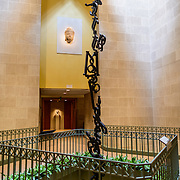 """Sackler Gallery Central Atrium. A portrait of The Buddha is on a wall and a symbolic display of hanging monkeys, each monkey being the word """"monkey in a different language"""" hangs in the central atrium of the Sackler Gallery. With nearly all of the gallery being underground, teh atrium also serves as a skylight to bring natural sunlight down several levels. The Arthur M. Sackler Gallery, located behind the Smithsonian Castle, showcases ancient and contemporary Asian art. The gallery was founded in 1982 after a major gift of artifacts and funding by Arthur M. Sackler. It is run by the Smithsonian Institution."""