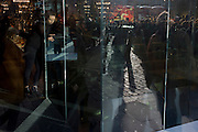 Christmas shoppers seen through the sunlit window of a central London Covent Garden retailer.