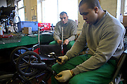 An inmate dismantles a wheel chair for reconditioning in the  Inside Out trust workshop.