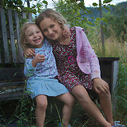Two sisters enjoying an apple at harvest time, sitting on an old bench by the orchard.