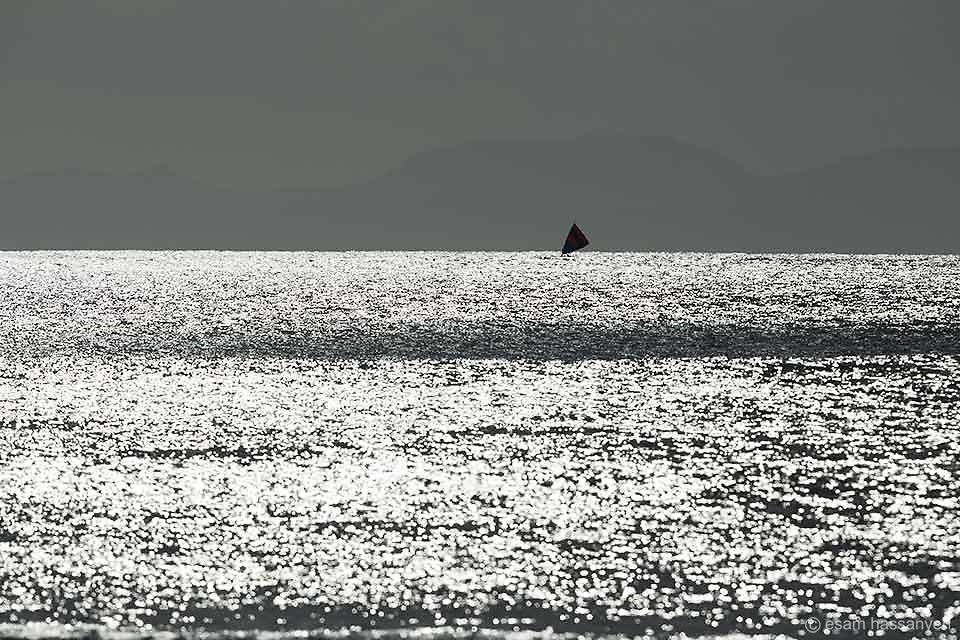 A lone sailing boats on a shimmering sea at sunset on the island of Lombok, Indonesia