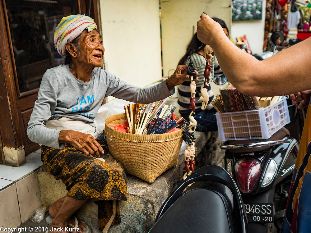 17 JULY 2016 - UBUD, BALI, INDONESIA:  An elderly Balinese woman tries to sell souvenirs to a tourist in the tourist market in Ubud, Bali.     PHOTO BY JACK KURTZ