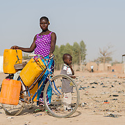 Juliette Ilboudo, pictured with her son Herman on 18 February 2016, uses her bicycle to wheel jerry cans to and from a water pump some distance from their home in the informal settlement of Zongo in Burkina Faso's capital, Ouagadougou. Fetching water for the household is a time-consuming and laborious task which falls primarily on the shoulders of women and girls. Heavily pregnant, Juliette says she finds fetching water a particularly difficult task, and often has to stop to rest or ask for help.