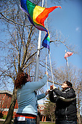 Leah Krandell '09 and Erin Duran '09 kick off the beginning of Pride Week at Grinnell College by raising the Pride flag near the College Bookstore and ARH.