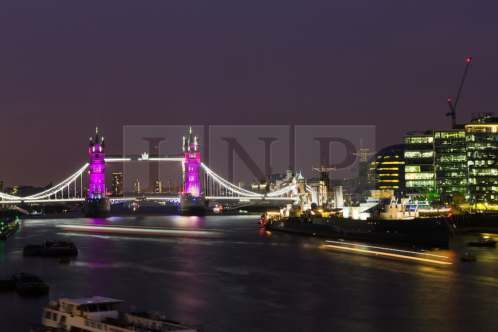 © Licensed to London News Pictures. 02/05/2015. London, UK. Tower Bridge in London is seen illuminated in pink next to HMS Belfast as boats pass on the River Thames to celebrate the birth of a baby daughter to Catherine Duchess of Cambridge and Prince William today. Photo credit : Vickie Flores/LNP