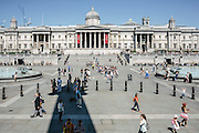 "A view of the National Gallery from Trafalgar Square. The square was built around the area formerly known as Charing Cross. At its centre is Nelson's Column, which is guarded by four lion statues at its base. The square is also used for political demonstrations and community gatherings, such as the celebration of New Year's Eve. The name commemorates the Battle of Trafalgar, a British naval victory of the Napoleonic Wars over France and Spain which took place on 21 October 1805 off the coast of Cape Trafalgar, Spain. The original name was to have been ""King William the Fourth's Square"", but George Ledwell Taylor suggested the name ""Trafalgar Square""."