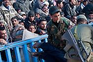 Un homme évanoui est évacué par les bénévoles Tunisiens. Poste Frontière de Ras Jedir, les réfugiés sont des milliers du coté Libyen de la frontière. Les militaires Tunisiens et les bénévoles sont obligés de fermer la frontière afin de pouvoir organiser leur accueil dans de bonnes conditions. Plus de 140 000 réfugiés ont déjà quitté la Libye par la Tunisie ou l'Egypte et des milliers continuent d'arriver chaque jours. Mardi 1er Mars 2011, poste frontière de Ras Jedir, Tunisie..© Benjamin Girette / AP