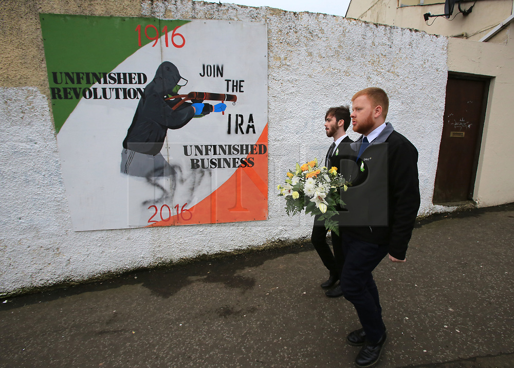 © Licensed to London News Pictures. 23/03/2017. Londonderry, UK. People walk pass a IRA mural in the Bogside area of Londonderry, Northern Ireland, 23 March 2017 ahead of the funeral of Sinn Féin's Martin McGuinness. Sinn Fein's Martin McGuinness, Northern Ireland's former deputy first minister, died aged 66 on 21 March 2017.. Photo credit: LNP