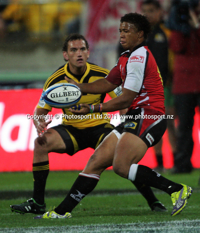Lions first five Elton Jantjies passes under pressure from Aaron Cruden. Super 15 rugby match - Hurricanes v Lions at Westpac Stadium, Wellington, New Zealand on Saturday, 4 June 2011. Photo: Dave Lintott / photosport.co.nz