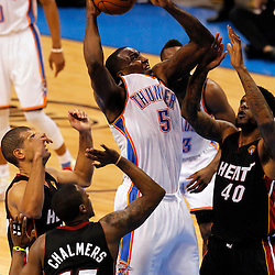 Jun 14, 2012; Oklahoma City, OK, USA;  Oklahoma City Thunder center Kendrick Perkins (5) shoots against Miami Heat point guard Mario Chalmers (15) and power forward Udonis Haslem (40) during the third quarter of game two in the 2012 NBA Finals at Chesapeake Energy Arena. Mandatory Credit: Derick E. Hingle-US PRESSWIRE
