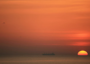 As the sun rises or sets on a firey sea, a cargo ship sails the horizon.
