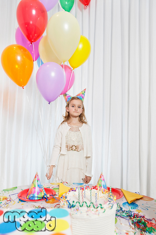 Portrait of a young girl holding party balloons with cake on table