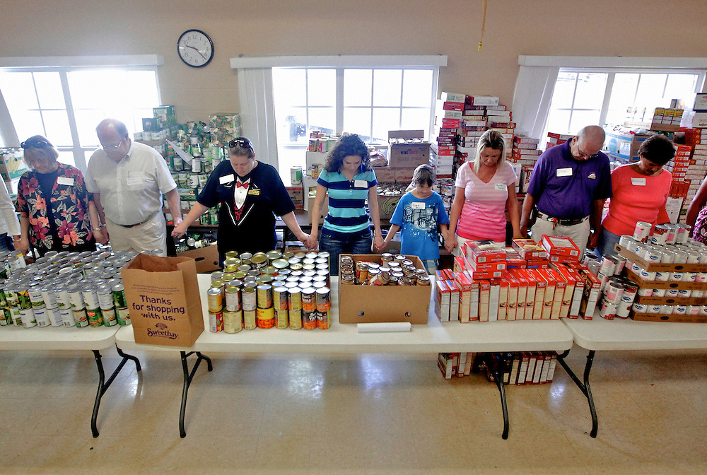 Volunteers pray before bagging donated food at St. Matthew's House, a food pantry and shelter for the homeless in Naples, Fla. Administrators for the shelter said some people who donated food last year, were now signing up to receive this year. Greg Kahn/Staff